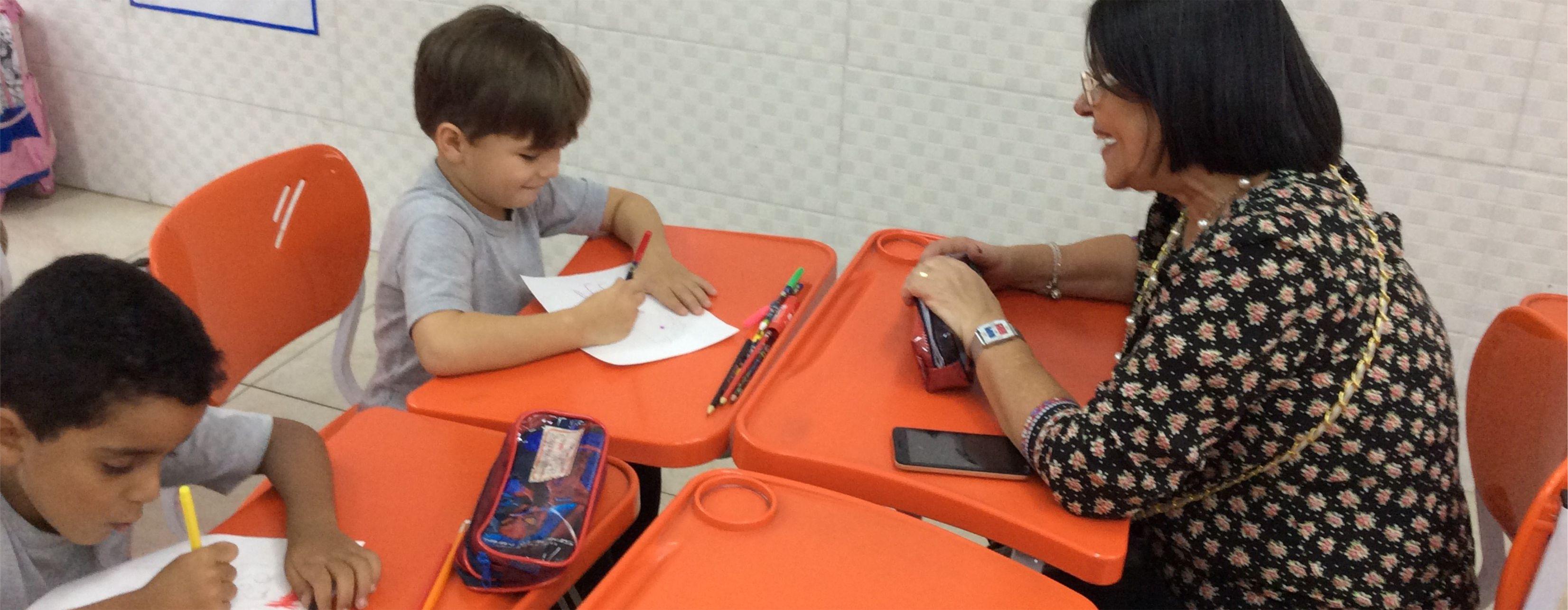 Avó orienta neto do Pré da Educação Infantil Certus a fazer lição
