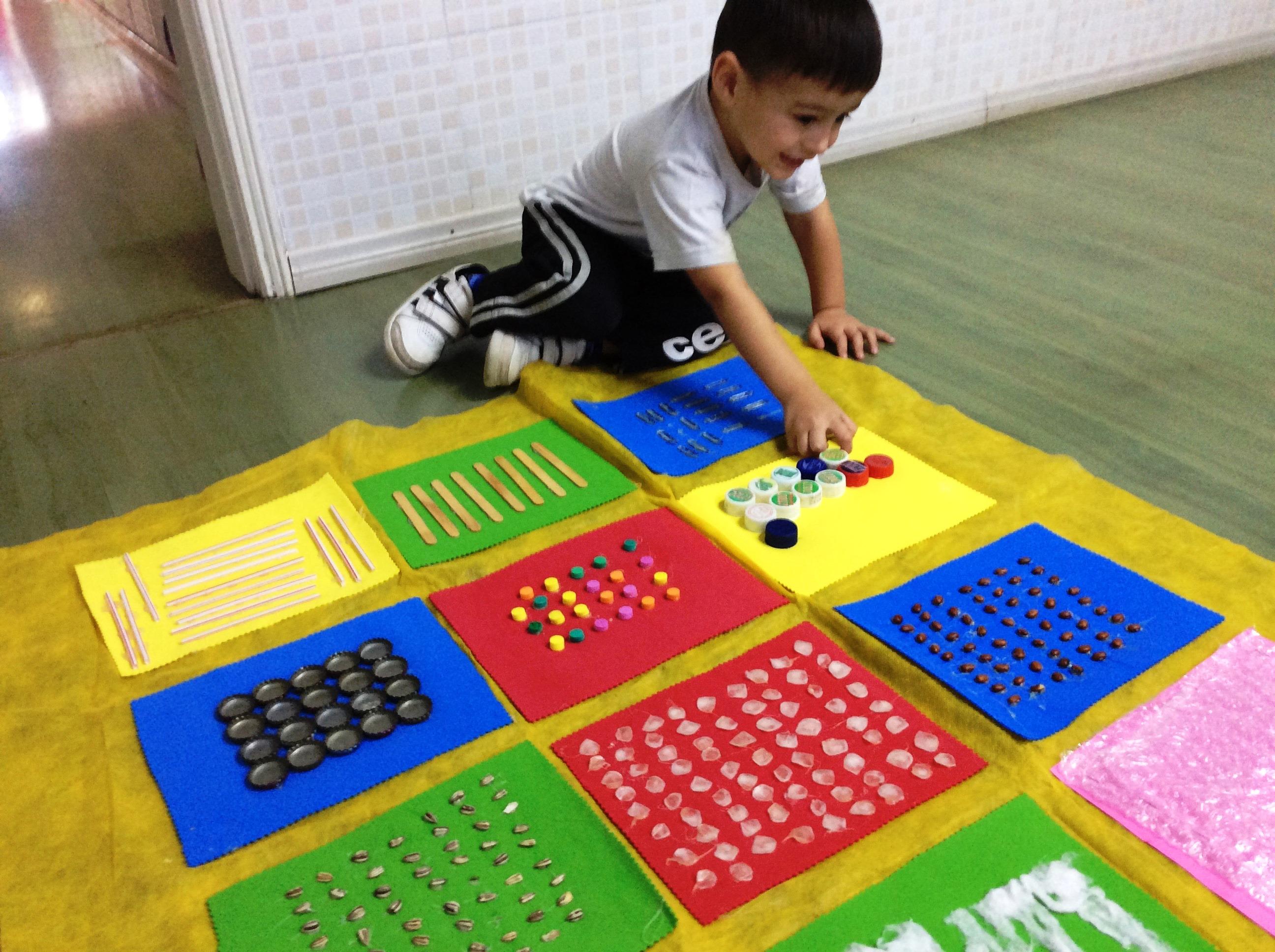 Criança brinca com tapete sensorial